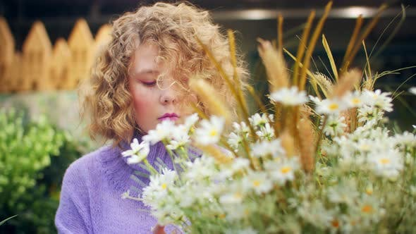 Young Woman with Blond Curly Looking Blooming Chamomile in Orangery