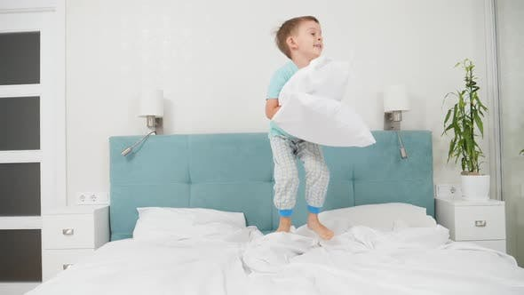 Thumbnail for SLow Motion of Cheerful Toddler Boy Holding Pillow and Jumping Up High on Bed at Parent's Bedroom