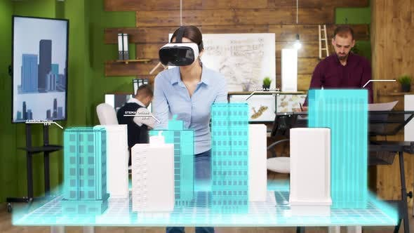 Architect Woman Wearing VR Headset Is Looking at Holographic Projections of Building a City