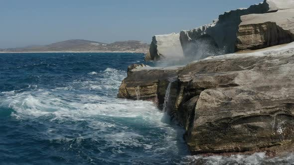 Aerial View of White Chalk Cliff with Waves Crashing on Rocks in Mykonos, Greece