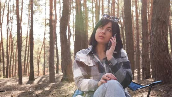 Bussiness woman having phone call, speking, sitting in chair in pine forest