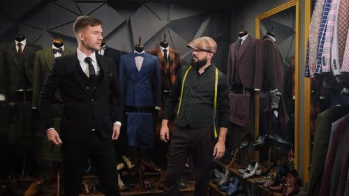Tailor Helps the Client Choose a Classic Three-piece Suit in an Atelier, Creative Adult Stylist