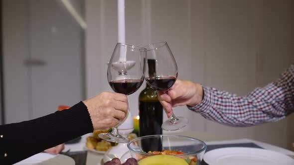 Thumbnail for Close Up of Clinking Red Wine Glasses During Romantic Dinner. Happy Cheerful Senior Elderly Couple