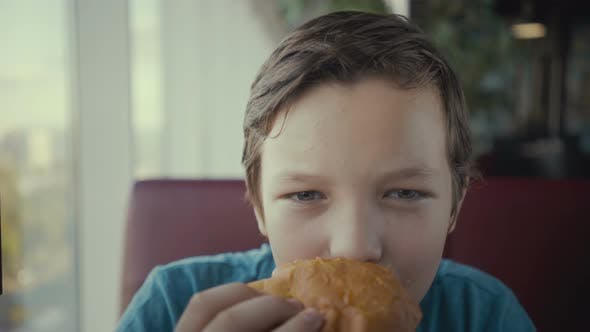 Thumbnail for Footage Happy Young Teenager Eating Tasty Burger in Fast Food Restaurant