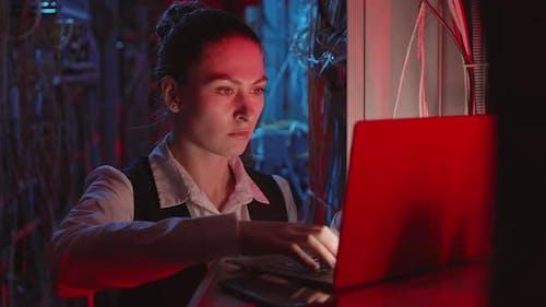 Female Programmer Coding in Server Room