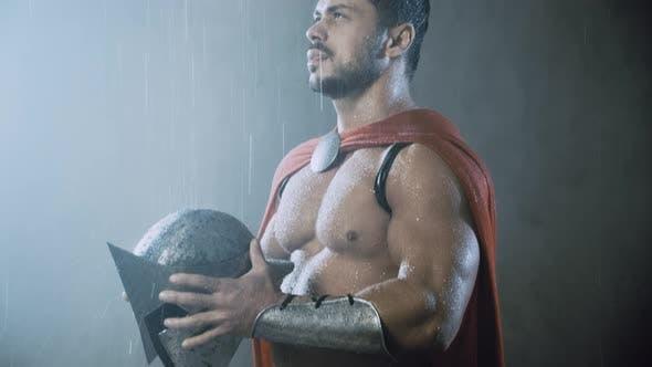 Cover Image for Wet Spartan Holding Helmet Under Rain.