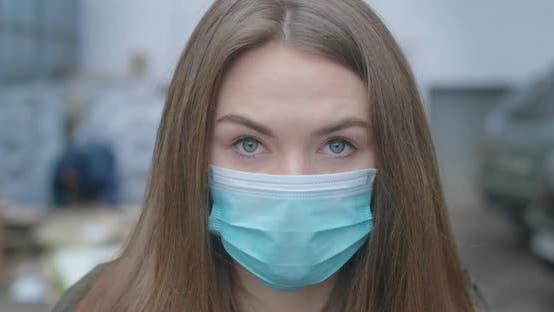 Cover Image for Close-up Face of Girl in Protective Mask Looking at Camera. Young Beautiful Brunette Woman with Grey