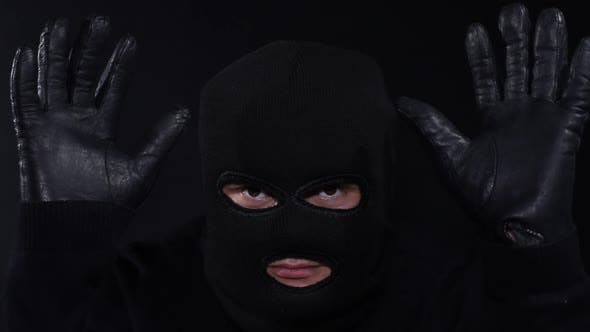 A criminal in a mask with a knife, a crazy maniac, touching his face with a knife in masks
