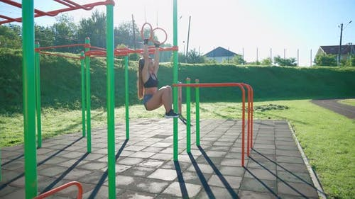 Woman Hanging Off Gymnastic Rings Pulling Legs Up