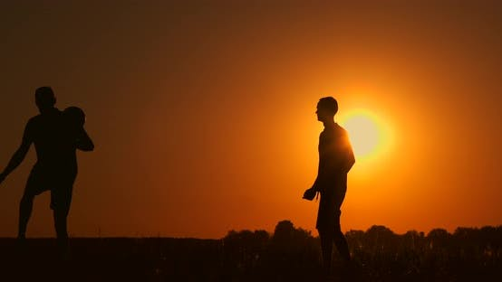 Cover Image for Two Boys Playing Soccer at Sunset. Silhouette of Children Playing with a Ball at Sunset. The Concept