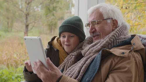 Child and Grandfather Sitting on Terrace and Using Tablet