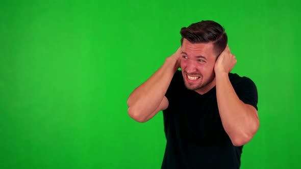Thumbnail for Young Handsome Caucasian Man Is Afraid (Man Covers His Ears) - Green Screen