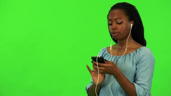 Thumbnail for A Young Black Woman Listens To Music on a Smartphone - Green Screen Studio