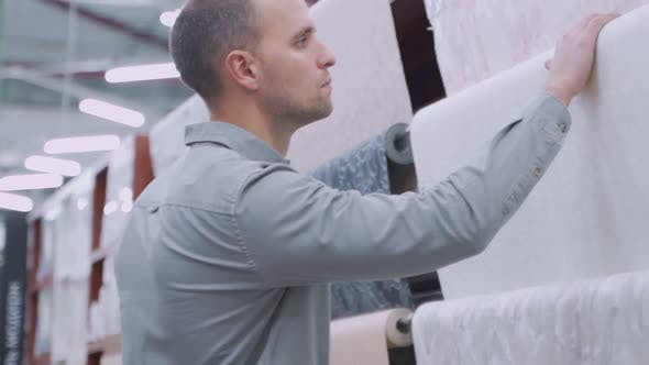 Male Consumer Buying Wallpapers In Hardware Store