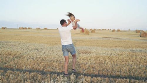 Happy Father Whirls His Daughter in Hands in a Field with Stubbles