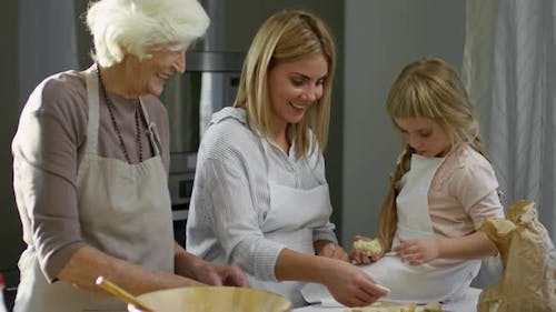 Three Generations of Women Cooking Together at Home