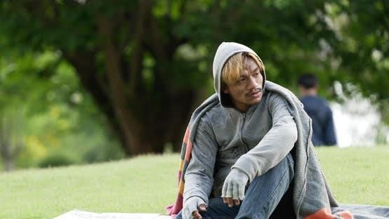Homeless man sitting on grass