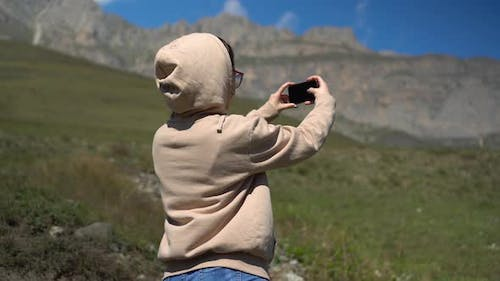 A Young Woman in a Sweatshirt Stands in the Mountains and Takes Pictures on the Phone.