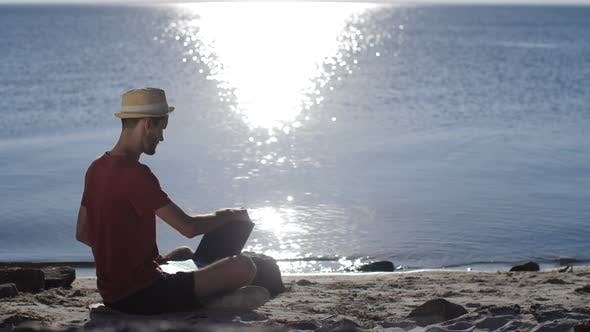 Thumbnail for Man Working with Laptop on the Beach at Sunset
