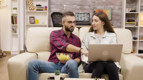 Happy Young Couple Sitting on Couch Doing Online Shopping