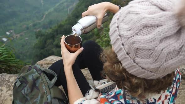 Thumbnail for Wanderer Sport Frau Sitzen Auf Mountain Peak Und Gießen Heißer Tee