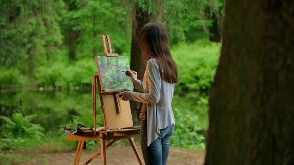 Thumbnail for Rear View of a Young Artist Woman Painting a Landscape