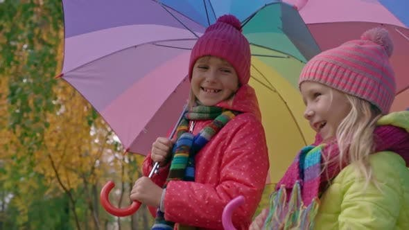 Thumbnail for Sisters with Umbrellas Walking in Park