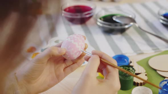 Unrecognizable Woman Painting Pattern on Easter Egg