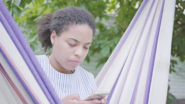 Thumbnail for Close-up Face of Young African American Woman Sitting in the Hammock, Relaxing in the Garden