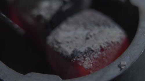 Shisha Hookah with Red Hot Coals Turning with Tongs Close-up. Hookah Hot Coals for Smoking Shisha