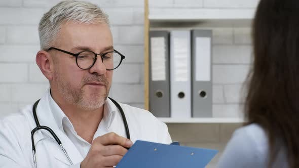 Male Doctor Talking With Sick Female Patient In Clinic