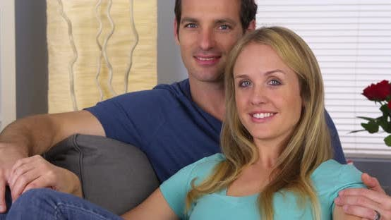 Thumbnail for Sweet couple sitting on couch looking at camera