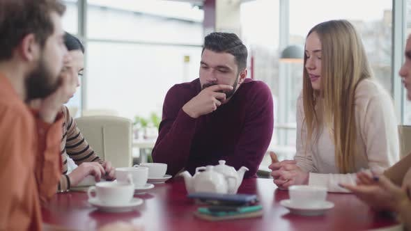 Thumbnail for Concentrated Caucasian Men and Women Sitting at the Table in Cafe and Looking at Gadgets Lying
