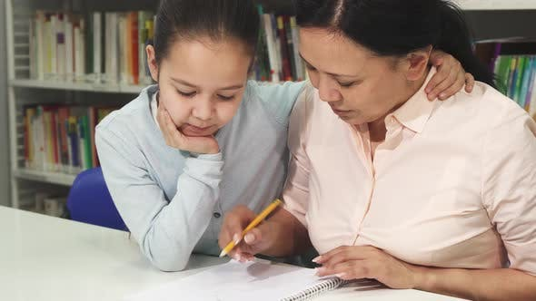 Happy Mature Asian Woman Helping Her Little Daughter with Studying