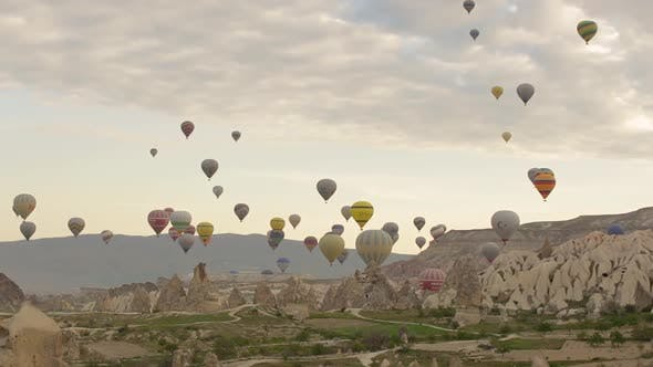 Hot-air balloons flying over the mountain landscape of Cappadocia, Turkey.