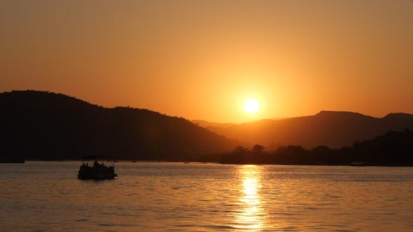 Cover Image for Beautiful sunset on the sea with boat silhouettes and hills.