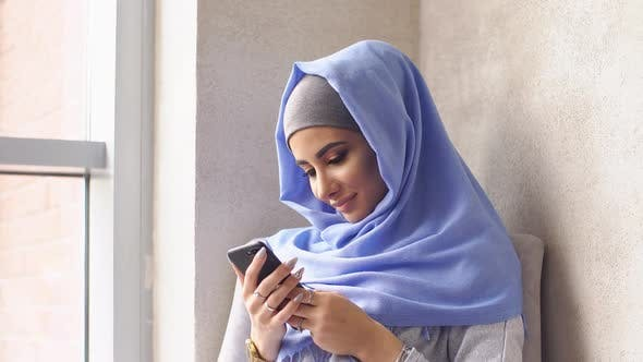 Thumbnail for Young Muslim Girl in Hijab Sends Message From Smartphone