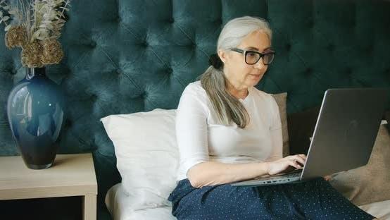 Elderly Woman Indoors with Laptop