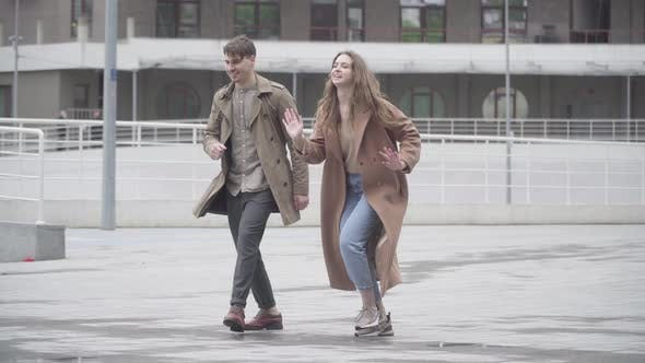 Thumbnail for Wide Shot of Cheerful Young Couple Dancing Outdoors on Urban City Street. Portrait of Positive
