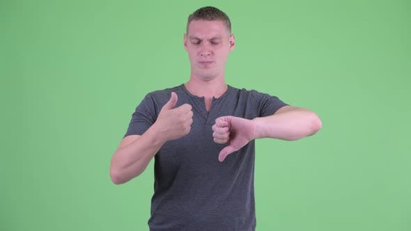 Thumbnail for Confused Young Man Choosing Between Thumbs Up and Thumbs Down