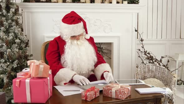 Thumbnail for Busy Santa Claus Checking Christmas Letters Sitting at His Table