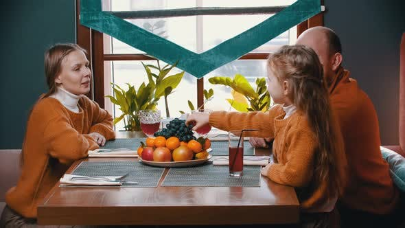 Thumbnail for A Happy Family Sitting in the Hotel Restaurant - a Little Girl Eating Grapes and Feeding Her Parents
