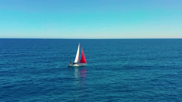 Cover Image for Yacht Sailing on Open Sea at Sunny Day. Sailing Boat with a Red Sail