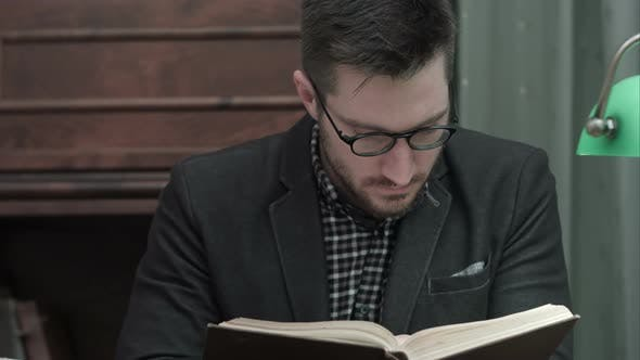 Thumbnail for Young Academic in Glasses Attentively Reading a Book