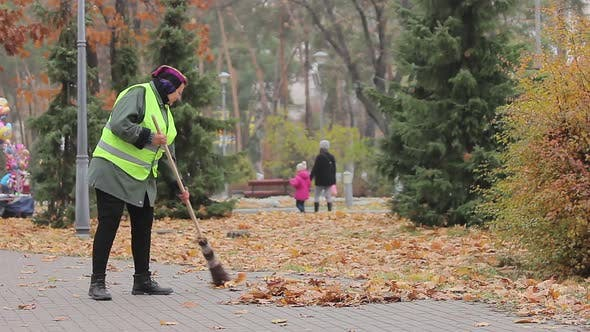 Thumbnail for Senior Woman Cleaning City Park, Stops to Have Rest, Looking at Beautiful Autumn