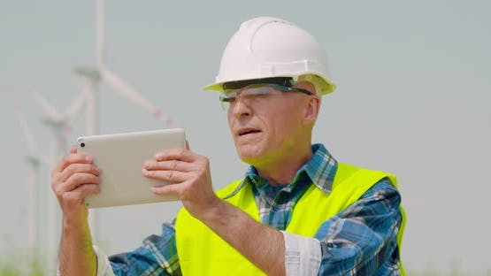 Male Engineer Video Conferencing Against Windmills