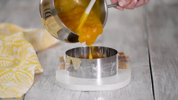 Pouring peach jelly into the metal ring, Making peach filling for mousse cake