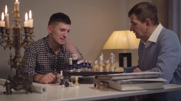 Thumbnail for Cheerful Caucasian Son and Father Playing Chess in the Evening at Home. Adult Man Spending Free Time
