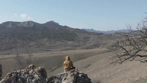Thumbnail for Man Sitting on the Big Stone and Enjoy the Scenery of the Mountain Range