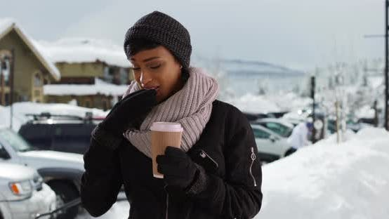 Thumbnail for Beautiful young woman in the snow with coffee, using smartphone